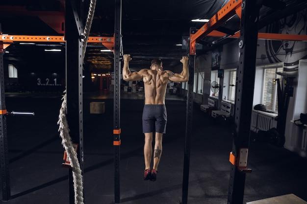 Junger gesunder mann, athlet, der übungen macht, klimmzüge im fitnessstudio. einzelnes kaukasisches modell, das hart übt und seinen oberkörper trainiert. konzept des gesunden lebensstils, sport, fitness, bodybuilding, wohlbefinden.