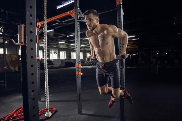 Junger gesunder mann, athlet, der übungen macht, klimmzüge im fitnessstudio. einzelnes männliches modell, das hart übt und seinen oberkörper trainiert. konzept des gesunden lebensstils, sport, fitness, bodybuilding, wohlbefinden.