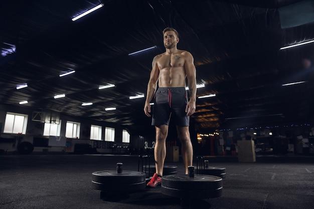 Junger gesunder mann, athlet, der übungen macht und mit langhantel im fitnessstudio aufwirft
