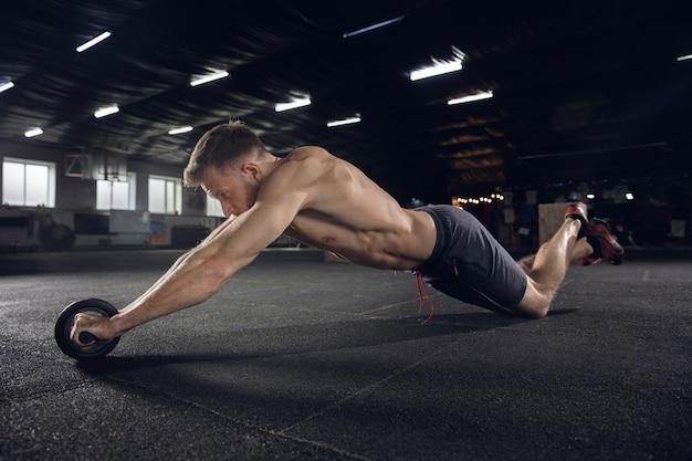 Junger gesunder mann, athlet, der übungen mit der walze im fitnessstudio macht