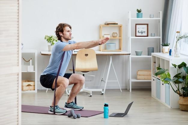 Junger gesunder mann, der sportübungen im wohnzimmer zu hause tut