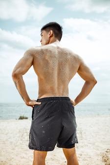 Junger gesunder mannathlet, der kniebeugen am strand tut