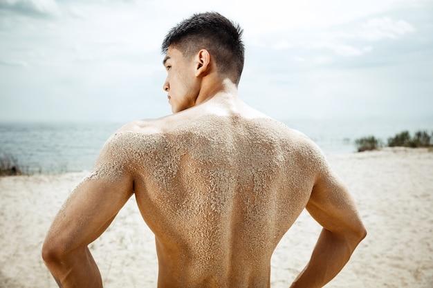 Junger gesunder mannathlet, der übung am strand tut