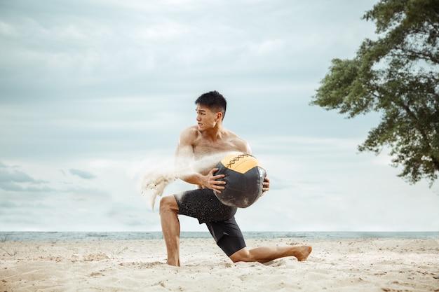Junger gesunder mannathlet, der übung mit ball am strand tut. hemdlose trainingsluft des männlichen modells des signels an der flussseite am sonnigen tag. konzept des gesunden lebensstils, des sports, der fitness, des bodybuildings.