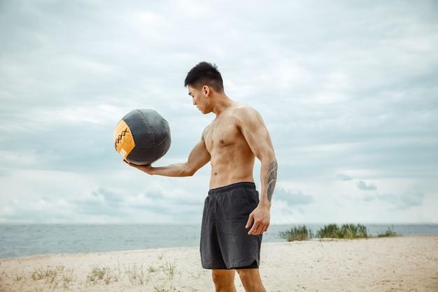 Junger gesunder mannathlet, der übung mit ball am strand tut