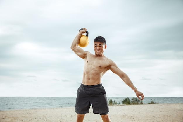 Junger gesunder mannathlet, der übung mit dem gewicht am strand tut. hemdloses training des männlichen modells des signels an der flussseite am sonnigen tag. konzept des gesunden lebensstils, des sports, der fitness, des bodybuildings.
