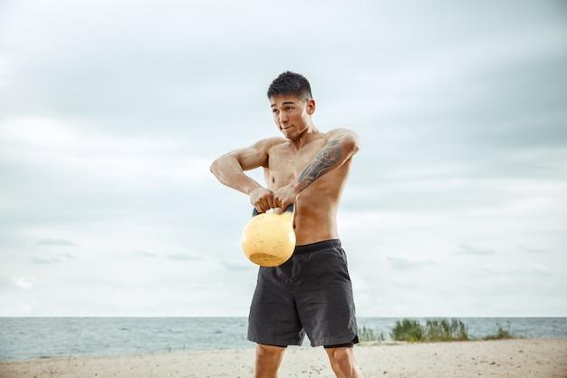Junger gesunder mannathlet, der übung mit dem gewicht am strand tut