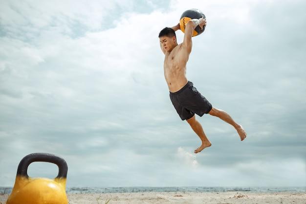 Junger gesunder mannathlet, der übung mit dem gewicht und ball am strand tut. hemdloses training des männlichen modells signle am flussufer. konzept des gesunden lebensstils, des sports, der fitness, des bodybuildings.