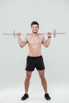 Junger gesunder mannathlet, der übungen mit langhantel tut