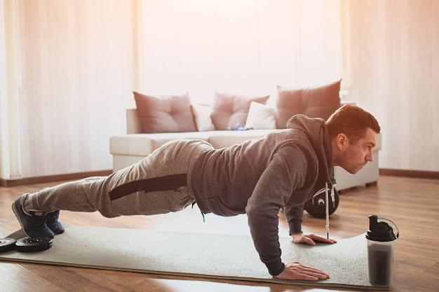 Junger gewöhnlicher mann, der sport zu hause macht. plankenposition auf seinen fäusten oder liegestütze machen.