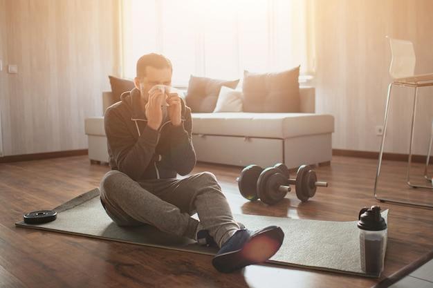 Junger gewöhnlicher mann macht zu hause sport. bild des punktanfängers, der auf matte sitzt und niest. krank und krank. grippe gefangen. unter schmerzen leiden. neuling im sport nach oder vor dem training wurde krank.