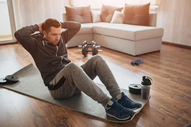 Junger gewöhnlicher mann macht zu hause sport. fleißiger neuling sitzt auf der matte und macht bauchmuskelübungen. es ist nicht einfach, alleine mit dem training zu beginnen. anfänger in aktion. sportausrüstung auf dem boden.