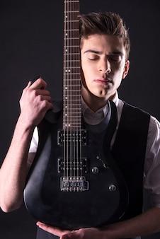 Junger gitarrist mit der e-gitarre.