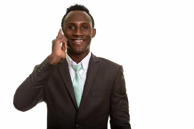 Junger glücklicher afrikanischer geschäftsmann, der lächelt, während auf handy spricht
