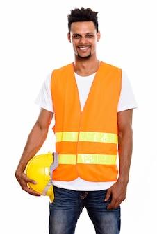 Junger glücklicher afrikanischer mannbauarbeiter, der lächelt, während er sicherheitshelm hält