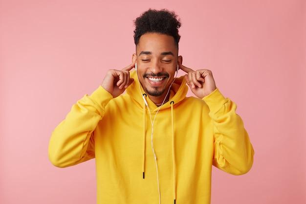 Junger glücklicher afroamerikanermann im gelben kapuzenpulli, der cooles neues lied seiner lieblingsband auf kopfhörern genießt