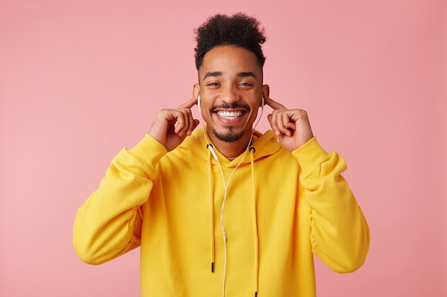 Junger glücklicher afroamerikanermann im gelben kapuzenpulli, der sein cooles lieblingslied auf kopfhörern genießt, die cavera betrachtet und breit lächelt