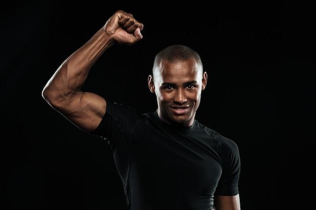 Junger glücklicher afroamerikanischer sportmann, der seinen sieg mit erhobenem arm feiert