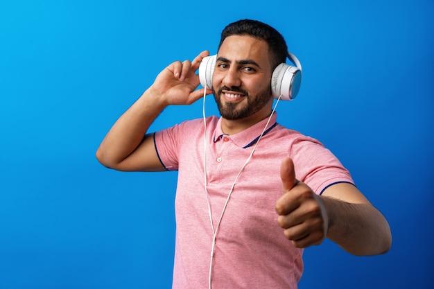 Junger glücklicher arabischer mann mit kopfhörern, die musik vor blauem hintergrund hören