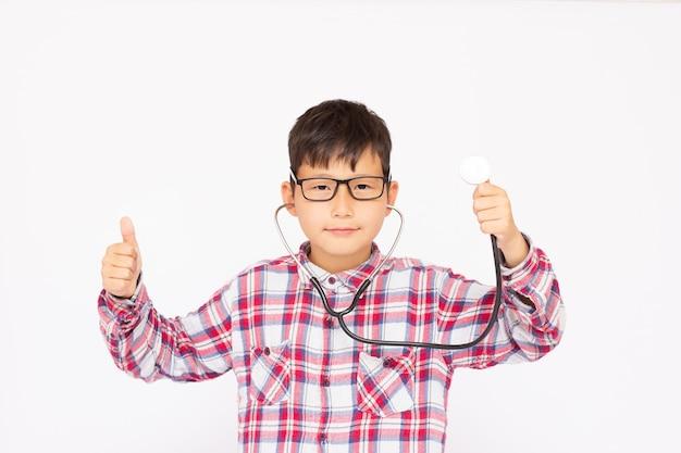Junger glücklicher asiatischer junge spielt einen arzt