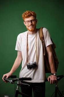 Junger glücklicher bärtiger mann mit lesekopf mit rucksack und retro-kamera