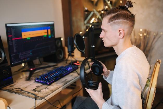 Junger glücklicher dj-mann, der kopfhörer trägt und zu hause arbeitet, während podcast-aufzeichnung für online macht