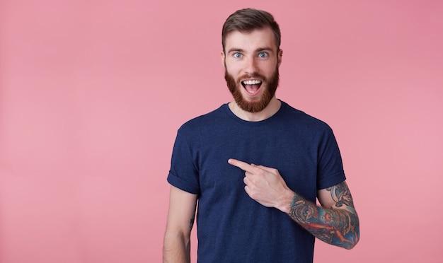 Junger glücklicher erstaunter attraktiver roter bärtiger junger mann, der ein blaues t-shirt mit dem weit geöffneten offenen mund trägt und finger zeigt, um raum auf der linken seite zu kopieren, der über rosa hintergrund isoliert wird.