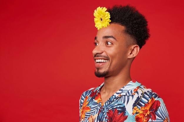 Junger glücklicher erstaunter dunkelhäutiger kerl, trägt im hawaiihemd, schaut mit glücklichem ausdruck in die kamera, mit einer gelben blume im haar, steht über rotem hintergrund.