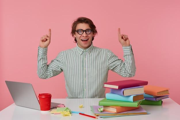 Junger glücklicher erstaunter student in der brille, sitzt am tisch und arbeitet mit laptop, schaut in die kamera und möchte sie aufmerksamkeit auf copispee über seinem kopf lenken, isoliert über rosa hintergrund.