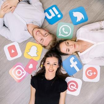 Junger glücklicher freund, der auf boden mit social media-logos liegt