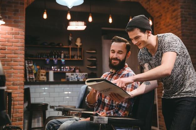 Junger glücklicher friseur und gutaussehender zufriedener kunde, der durch das magazin schaut, das im friseursalon sitzt