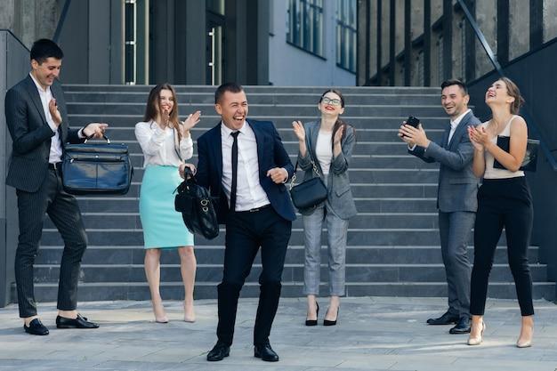 Junger glücklicher geschäftsmanager, der einen anzug und einen krawattentanz vom bürogebäude trägt. kollegen jubeln. vielfältige und motivierte geschäftsleute aus dem modernen büro.