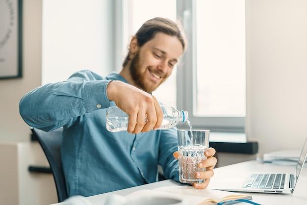 Junger glücklicher geschäftsmann, der an seinem arbeitsplatz wasser in glas gießt