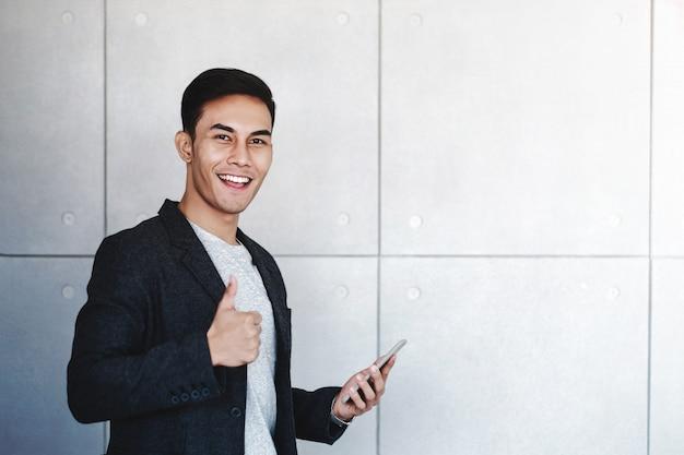 Junger glücklicher geschäftsmann smiling und show thumbs up bei der anwendung von smartphone