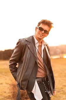 Junger glücklicher hipster-mann in vintage-sonnenbrille mit frisur in modischer schwarzer lederjacke entspannt sich im freien bei sonnenuntergang. netter kerl mit lächelnrest und genießt die leuchtend orange frühlingssonne auf der natur.