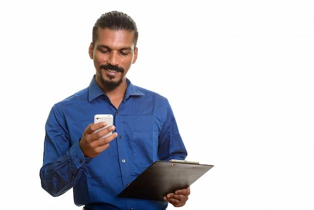 Junger glücklicher indischer geschäftsmann, der handy beim halten der zwischenablage verwendet