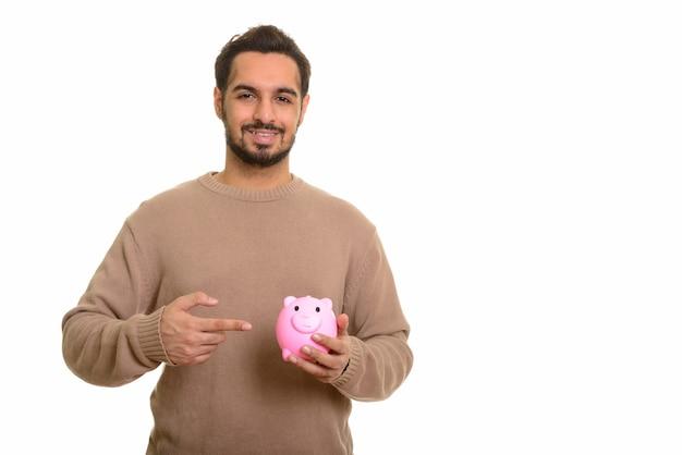 Junger glücklicher indischer mann, der sparschwein hält und zeigt