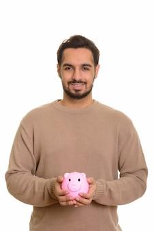 Junger glücklicher indischer mann, der sparschwein hält