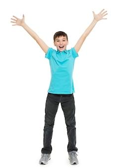 Junger glücklicher jugendlicher junge mit in lässigen mit erhabenen händen oben isoliert auf weiß.