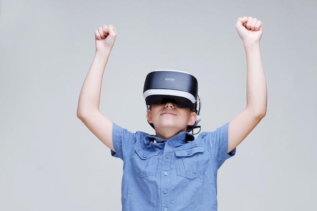 Junger glücklicher junge in gläsern der virtuellen realität auf grauem hintergrund