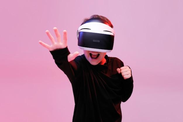 Junger glücklicher junge in gläsern der virtuellen realität auf neollichthintergrund