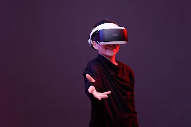 Junger glücklicher junge in gläsern der virtuellen realität auf schwarzem hintergrund
