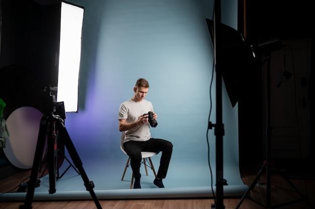 Junger glücklicher kaukasischer mann, der im studio aufwirft. backstage-konzept.