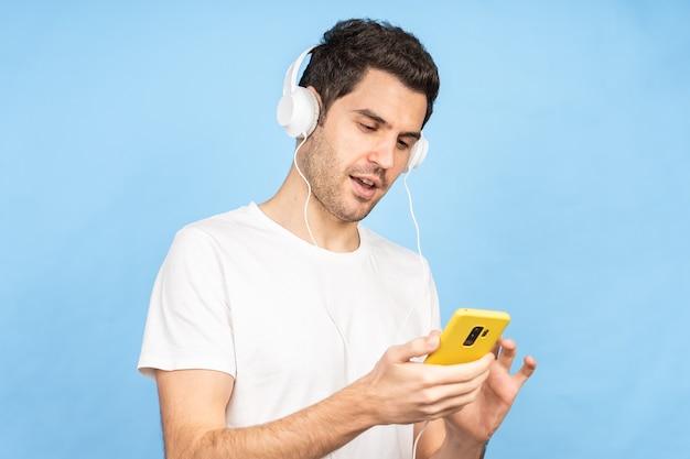 Junger glücklicher kaukasischer mann, der musik mit kopfhörern gegen eine blaue wand hört