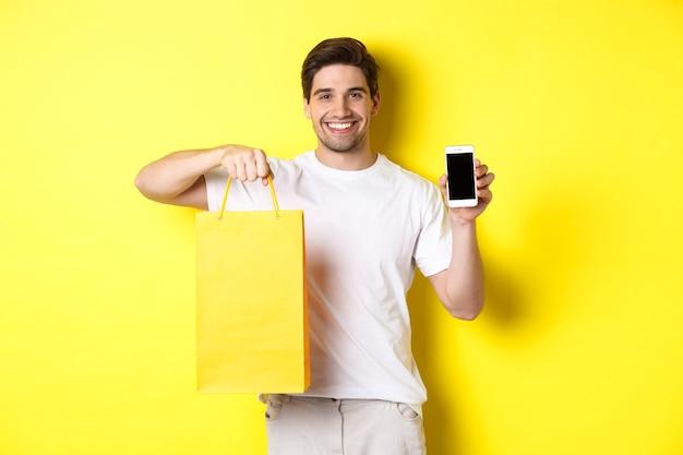 Junger glücklicher kerl, der einkaufstasche hält und smartphonebildschirm, gelbe wand zeigt