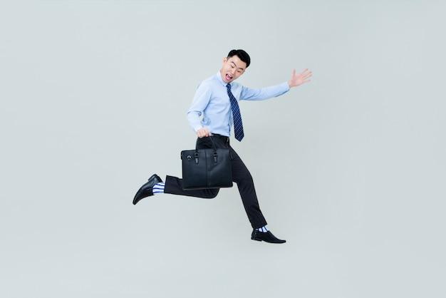 Junger glücklicher lächelnder asiatischer berufsmann, der in der luft springt