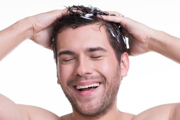 Junger glücklicher lächelnder mann, der haare mit geschlossenen augen wäscht - lokalisiert auf weiß.
