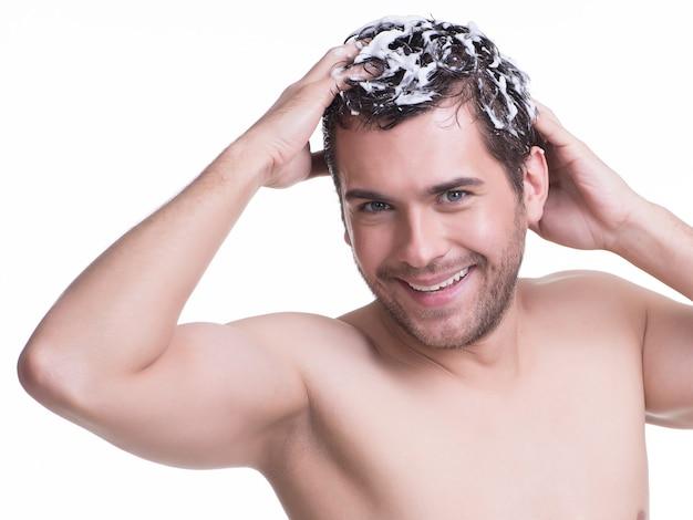 Junger glücklicher lächelnder mann, der haare mit shampoo wäscht - lokalisiert auf weiß.