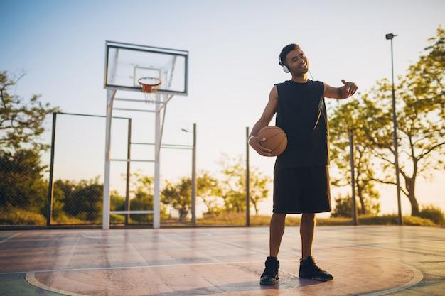 Junger glücklicher lächelnder schwarzer mann, der sport macht, basketball bei sonnenaufgang spielt, musik auf kopfhörern, aktivem lebensstil, sommermorgen hört