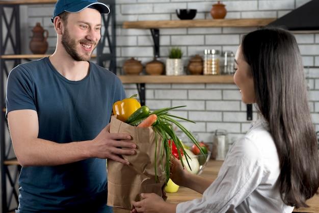 Junger glücklicher lieferer, der zu hause der frau in der küche lebensmittelgeschäft gibt
